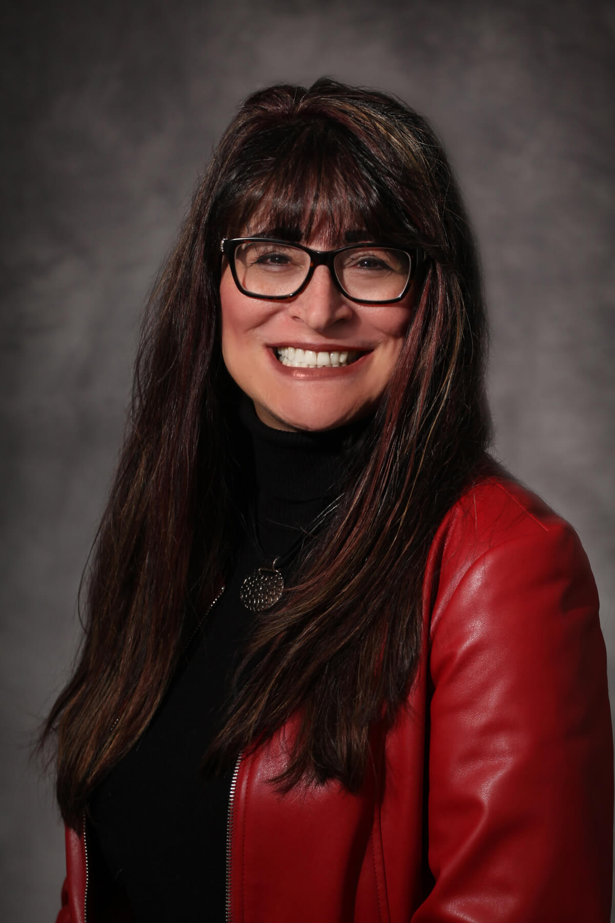Irene Richardson, woman with long voluminous brown hair and black glasses wearing a red leather jacket