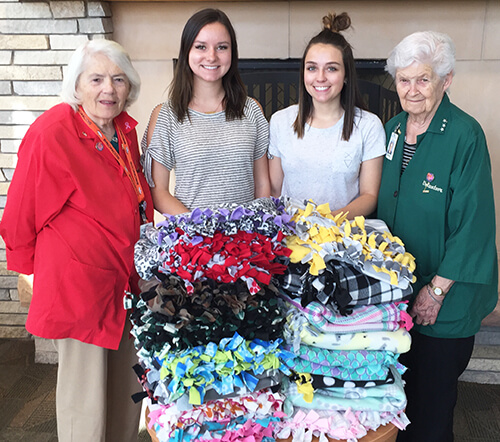 2 elderly ladies and 2 high school girls standing with a pile of handmade blankets